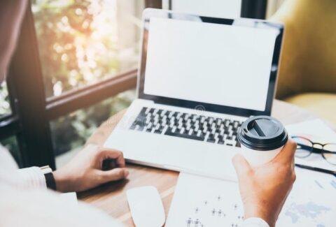 руки-бизнесмена-держа-чашку-кофе-и-используя-ноутбук-с-пустым-экраном-151999608